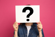 Woman Holding Question Mark Sign On Pink Background