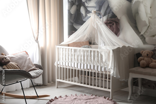Photo Baby room interior with stylish crib and floral wallpaper