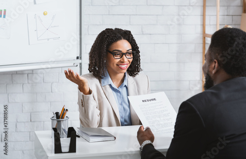 Friendly personnel manager interviewing black candidate during job interview at Canvas Print