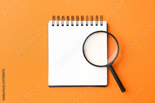 Fotografía Magnifier glass and empty notebook on orange background, flat lay with space for text
