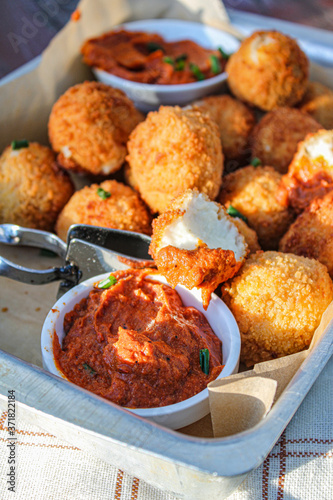 Cheese balls with tomato sauce. Fried snack starter meal. Party food © Irati