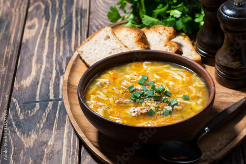 chicken soup with egg noodles on wooden background Fototapeta