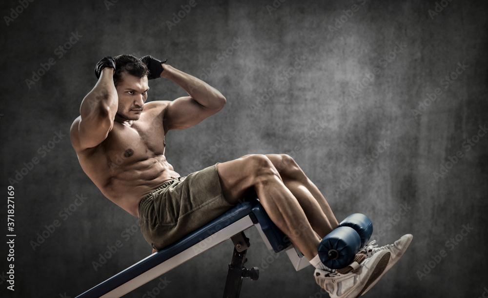 Fototapeta man bodybuilder perform exercise on prelum abdominale on bench