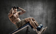man bodybuilder perform exercise on prelum abdominale on bench