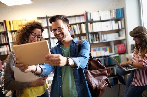 Young university students studying together Billede på lærred