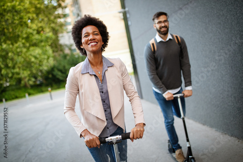 Happy young couple enjoying together while riding electric scooters on city stre Fototapeta