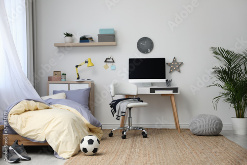 Leinwand Poster Stylish teenager's room interior with comfortable bed and workplace