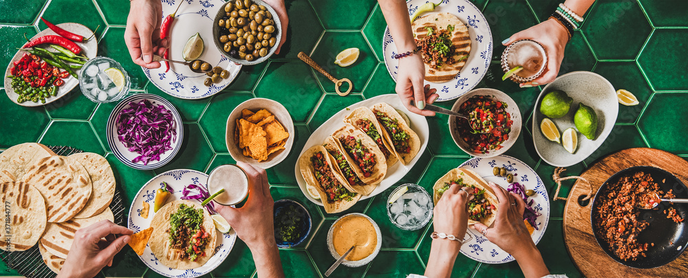 Fototapeta Family or friends home taco party. Flat-lay of Mexican traditional dishes Tacos with beef meat, corn tortillas , tomato salsa and peoples hands over green background, top view. Mexican cuisine concept