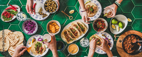 Family or friends home taco party. Flat-lay of Mexican traditional dishes Tacos with beef meat, corn tortillas , tomato salsa and peoples hands over green background, top view. Mexican cuisine concept