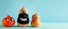 Funny Pumpkins With Faces And In A Black Protective Mask On Pastel Blue Background. Concept Celebration Of Halloween Or Thanksgiving In The Conditions Of Coronavirus.