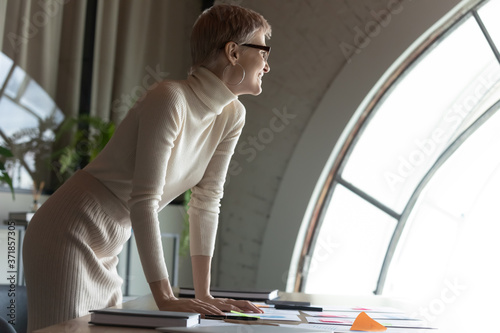 Canvastavla Happy dreamy young blonde businesswoman in eyewear leaning at table with paper r