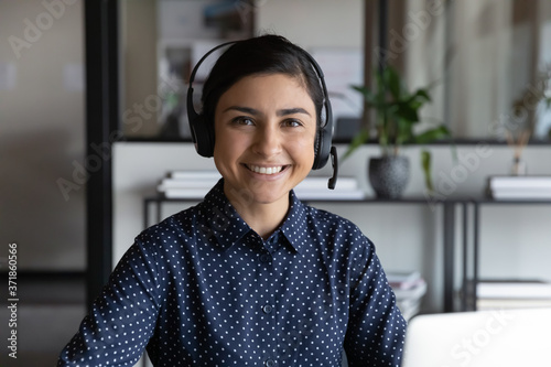 Fototapeta Head shot portrait of pleasant smiling young indian ethnicity attractive female employee wearing wireless headset with mic, professional consultant advisor hotline specialist looking at camera. obraz na płótnie