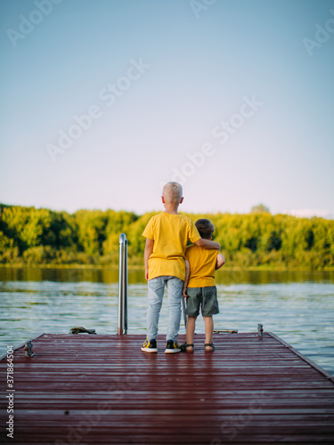 Cool kids brothers hug each other and look at the river staying on dock Canvas Print