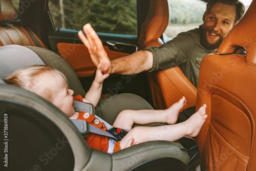 Fotografia Father with child in car on road trip high five hands baby sitting in safety sea