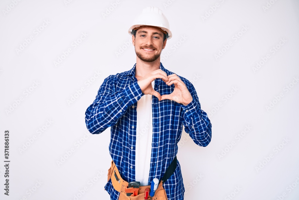 Fototapeta Young handsome man weaing handyman uniform smiling in love showing heart symbol and shape with hands. romantic concept.