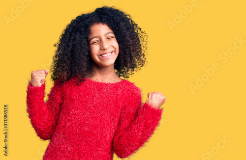 African american child with curly hair wearing casual winter sweater very happy and excited doing winner gesture with arms raised, smiling and screaming for success. celebration concept.