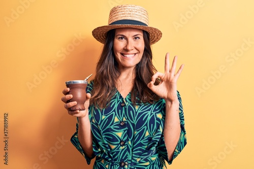 Fotografie, Obraz Young beautiful brunette woman wearing summer hat drinking cup of mate infusion