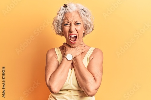 Senior grey-haired woman wearing casual clothes shouting suffocate because painful strangle Canvas Print