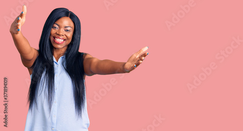 Obraz na plátně Young african american woman wearing casual clothes looking at the camera smiling with open arms for hug