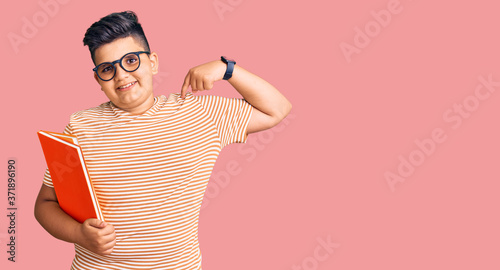 Fototapeta Little boy kid holding book wearing glasses looking confident with smile on face, pointing oneself with fingers proud and happy