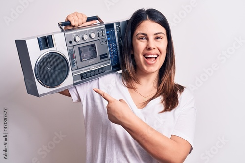 Photo Young beautiful woman listening to music using vintage boombox over white backgr
