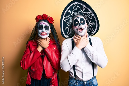 Couple wearing day of the dead costume over yellow shouting and suffocate because painful strangle Canvas Print