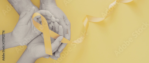 Fotomural adult and child hands holding yellow gold ribbon, Sarcoma Awareness, Bone cancer