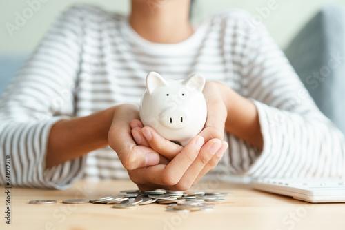 Asian girl holding piggy bank and saving money For future scholarships Fototapeta