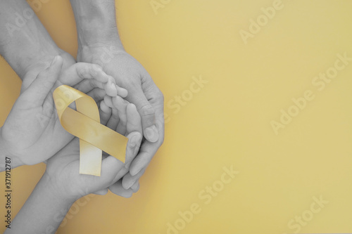 Fotografie, Obraz adult and child hands holding yellow gold ribbon, Sarcoma Awareness, Bone cancer