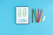Notebook And Paper Clips In The Form Of A Smiley With Stationery Or School Supplies On A Blue Background. Place For Your Text. Learning, Children Are Happy To Go To School.