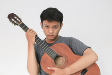 Young Asian Musician Who Is Sad By Hugging His Guitar