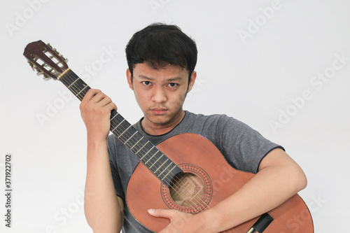 Canvas-taulu Young Asian musician who is sad by hugging his guitar