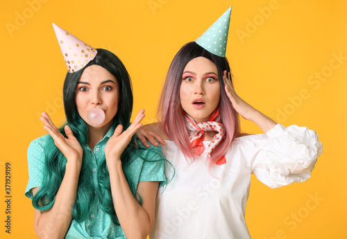 Foto Beautiful young women in party wigs on color background