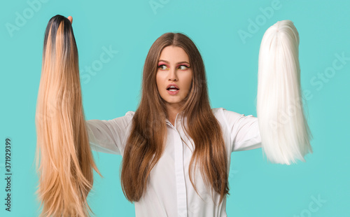 Beautiful young woman with different wigs on color background Fototapete