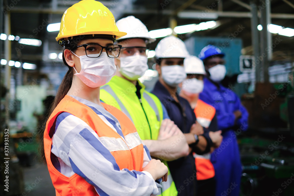 Fototapeta Industrial woman engineer or factory worker wearing helmet and hygiene face mask with men stand in line at manufacturing plant.People working industry during covid pandemic.