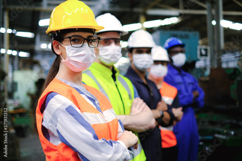 Cuadros en Lienzo Industrial woman engineer or factory worker wearing helmet and hygiene face mask with men stand in line at manufacturing plant