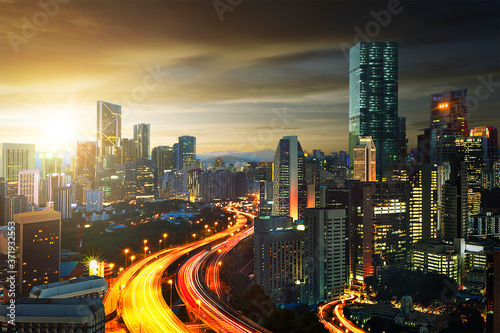 Fotografiet The light trails scenery at the busy highway in modern city during sunset