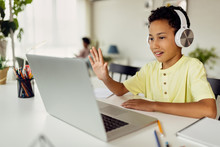 African American Boy Using Laptop And Waving During Video Call While Homeschooling.