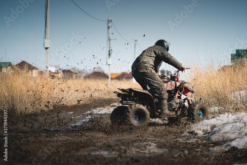 Motor biker is riding a quad bike on the dirty road. Fototapete