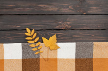 Woolen Checkered Plaid. Autumn Background. Checkered Yellow Brown Plaid With Golden Leaves On Dark Wooden Background Top View Copy Space Cozy Fall Composition Autumn Textile, Checkered Fabric Texture