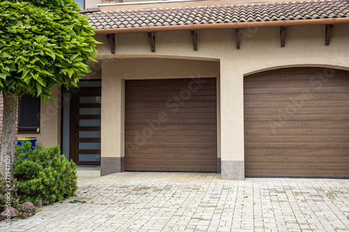 Fotomural Brick stone driveway double garage doors with green tree