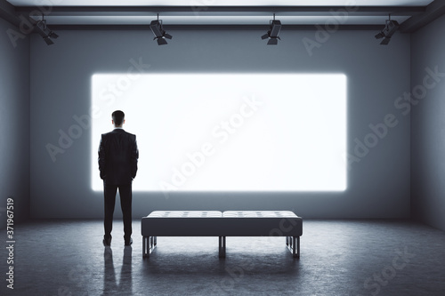 Tablou Canvas Businessman standing in modern exhibition room with blank projection screen