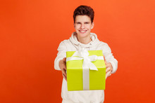 Satisfied Teenager In Casual White Hoodie Holding Out Present Box With Toothy Smile On Face, Delivery Service. Indoor Studio Shot Isolated On Orange Background