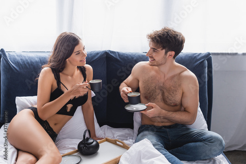 Foto muscular man and seductive woman holding cups with tea and looking at each other