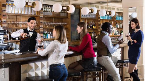 Happy cheerful smiling barman is servicing young people who are relaxing in bar indoor Fototapeta