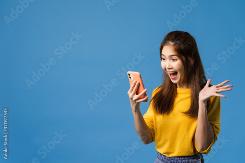 Surprised young Asia lady using mobile phone with positive expression, smiles broadly, dressed in casual clothing and standing isolated on blue background Fototapeta