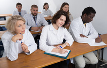 Portrait Of Focused Medics Sitting In Lecture Hall, Listening Specialty Workshop