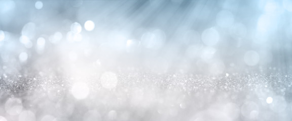 Bokeh effects on silver glittering background White bokeh effects on blue and silver glittering abstract background with rays of light. Background for wedding and christmas. Space for design and text.