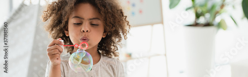 Tela panoramic shot of curly african american kid blowing soap bubbles