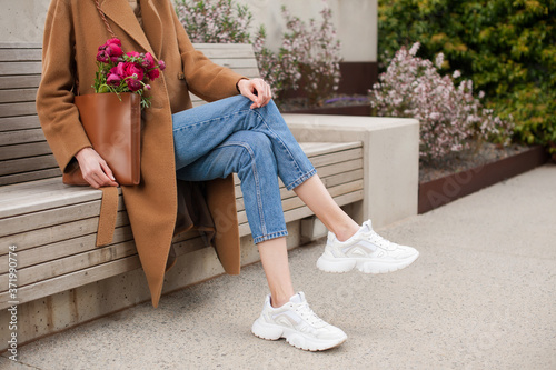 Fototapeta Fashionable young woman wearing beige wool coat and blue jeans